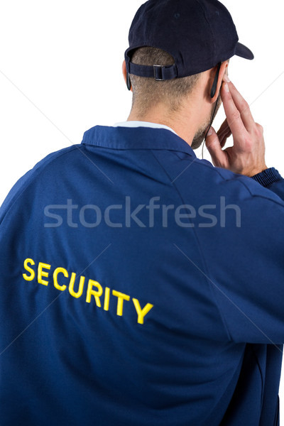 Rear view of security officer listening to earpiece Stock photo © wavebreak_media