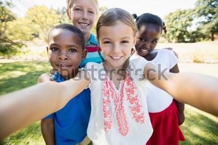 Aranyos iskolás mutat nagy poszter fű Stock fotó © wavebreak_media
