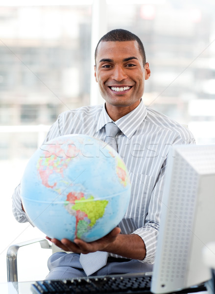 Ethnic businessman holding a terrestrial globe Stock photo © wavebreak_media