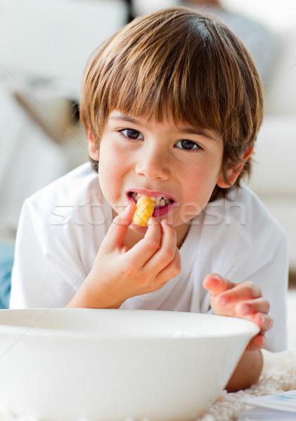 Cute little boy eating chips lying on the floor  Stock photo © wavebreak_media