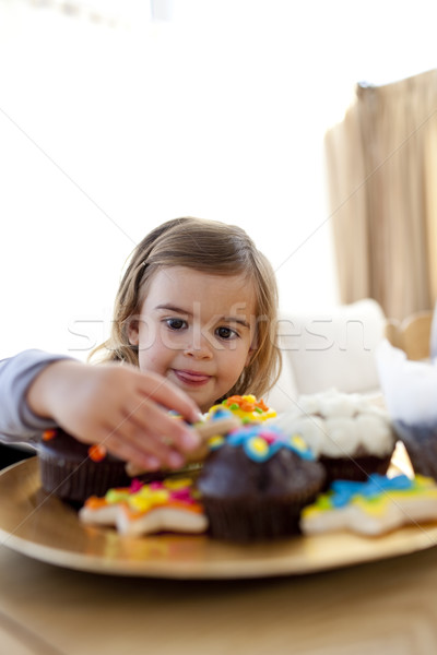 Hungry little girl looking at confectionery at home Stock photo © wavebreak_media