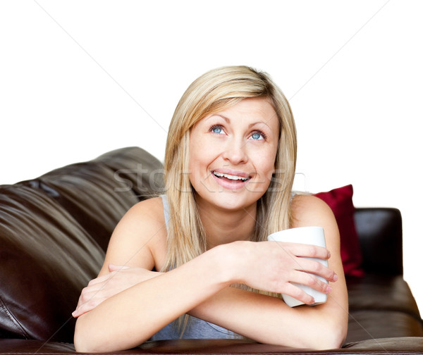 Laughing woman lies on a brown sofa at home Stock photo © wavebreak_media