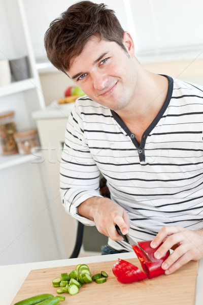 Smiling young man cutting vegetables in the kitchen at home Stock photo © wavebreak_media