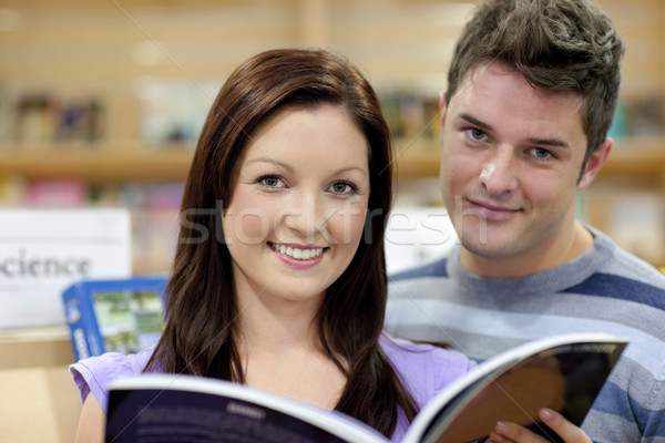 Portrait of a cute couple reading a book in a shop and smiling at the camera Stock photo © wavebreak_media