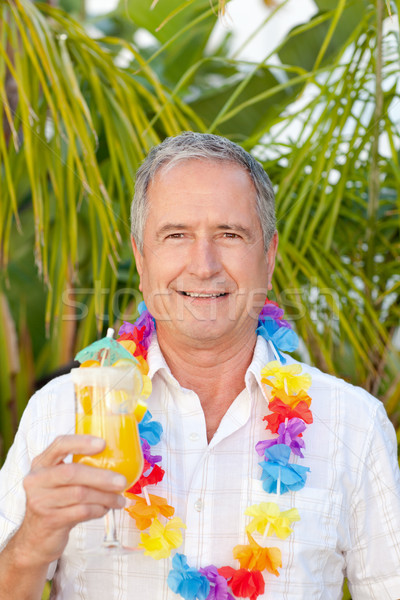 Stock photo: Mature man drinking a cocktail under the sun