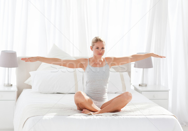 Beautiful woman practicing yoga on her bed at home Stock photo © wavebreak_media