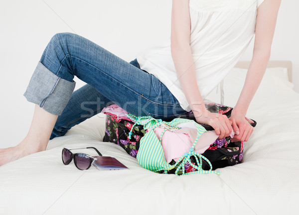 Good looking blonde female trying to close her suitcase in her bedroom in her appartment Stock photo © wavebreak_media