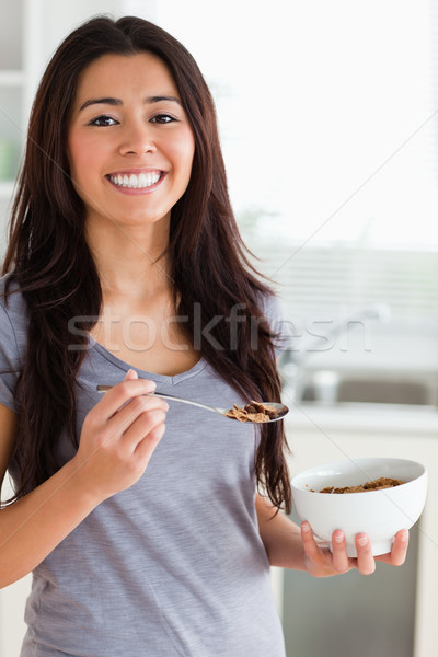 Gorgeous female enjoying a bowl of cereal while standing in the kitchen Stock photo © wavebreak_media