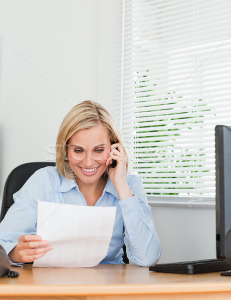 Businesswoman phoning and reeding a paper in her office Stock photo © wavebreak_media
