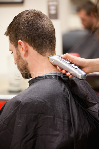 Portrait of man having a haircut with a hair clippers Stock photo © wavebreak_media