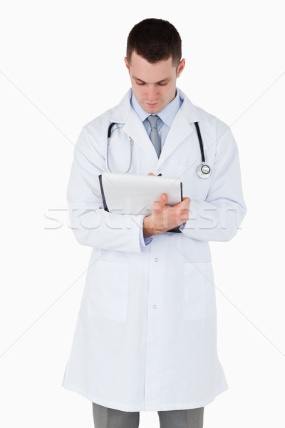 Doctor taking a careful look at his notes on white background Stock photo © wavebreak_media