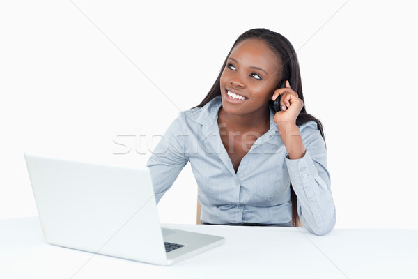 Smiling businesswoman making a phone call while using a laptop against a white background Stock photo © wavebreak_media