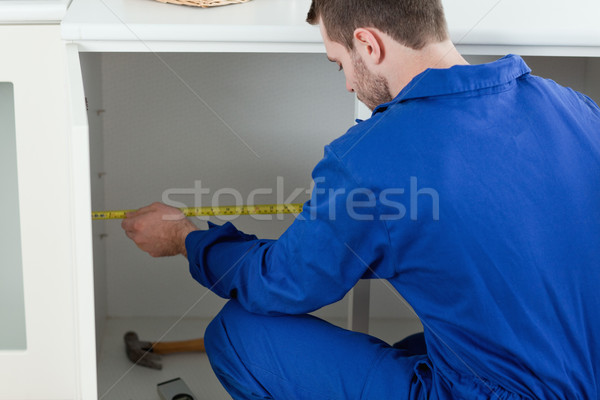 Stock photo: Focused repair man measuring something in a kitchen