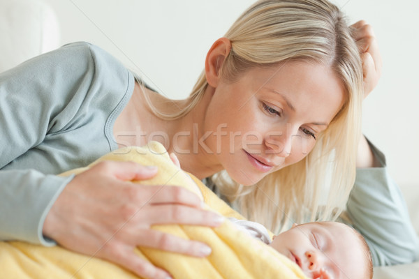 Young mom relaxing next to her sleeping baby Stock photo © wavebreak_media