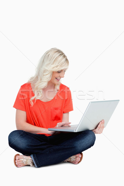 Young woman sitting cross-legged with her laptop against a white background Stock photo © wavebreak_media