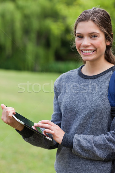 Young smiling girl using her tablet computer while standing upright in a park Stock photo © wavebreak_media