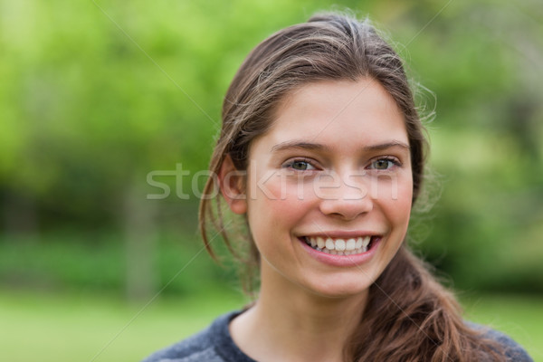 Young woman looking at the camera while showing a beaming smile Stock photo © wavebreak_media