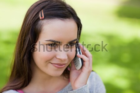 Young relaxed girl talking on the phone while standing upright in a parkland Stock photo © wavebreak_media