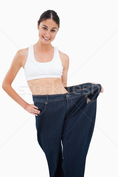 Young woman has lost a lot of weight against white background Stock photo © wavebreak_media