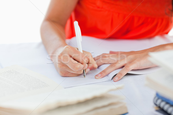 Close-up of a pen using by a student to do her homework against white background Stock photo © wavebreak_media