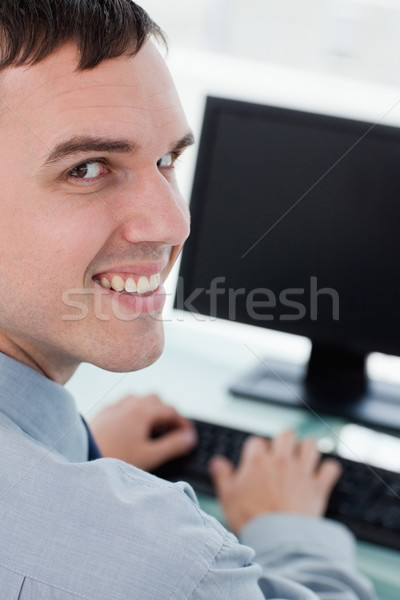 Back view of a smiling businessman using a monitor in his office Stock photo © wavebreak_media