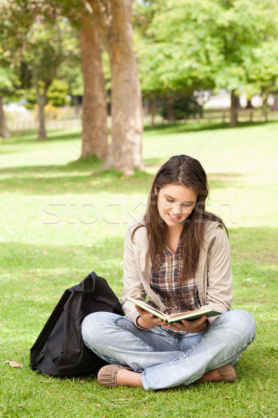 Teenager sitting while reading a textbook in a park Stock photo © wavebreak_media