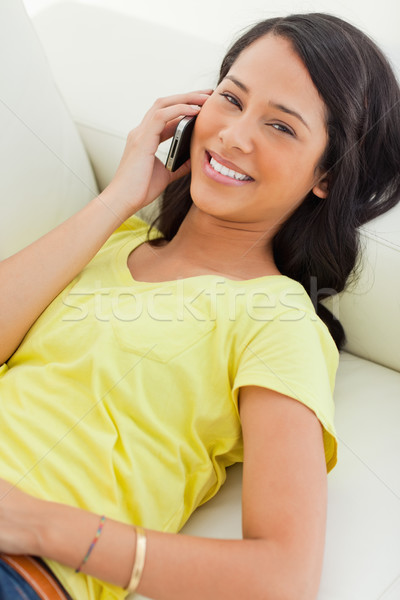 Portrait of a smiling Latino on the phone while lying on a sofa Stock photo © wavebreak_media