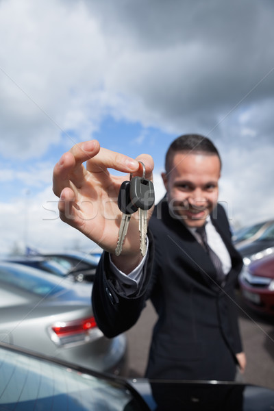 happy dealer holding car keys by his fingertips outddors Stock photo © wavebreak_media