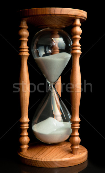 Sand flowing inside of hourglass against a black background Stock photo © wavebreak_media