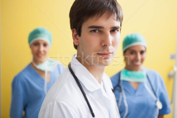 Doctor in labcoat with two smiling nurses in scrubs in background Stock photo © wavebreak_media