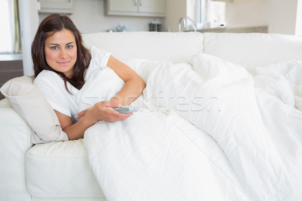 Woman relaxing on the sofa and holding a remote while watching television Stock photo © wavebreak_media