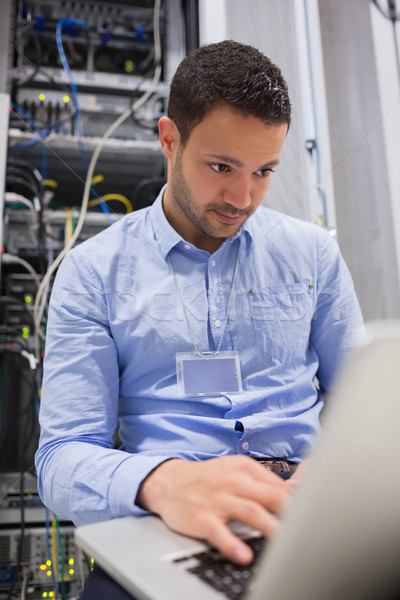 Man working on laptop in front of servers in data center Stock photo © wavebreak_media