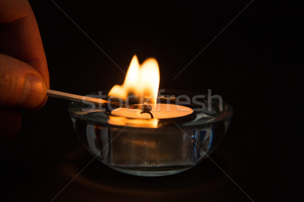 Hand lighting tea light candle in the dark Stock photo © wavebreak_media