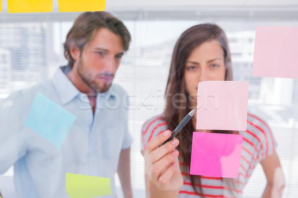 Woman pointing a sticky note Stock photo © wavebreak_media
