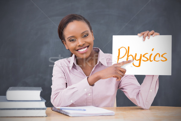 Happy teacher holding page showing physics Stock photo © wavebreak_media
