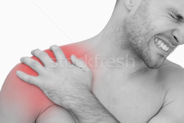 Jovem sem camisa homem dor no ombro branco Foto stock © wavebreak_media