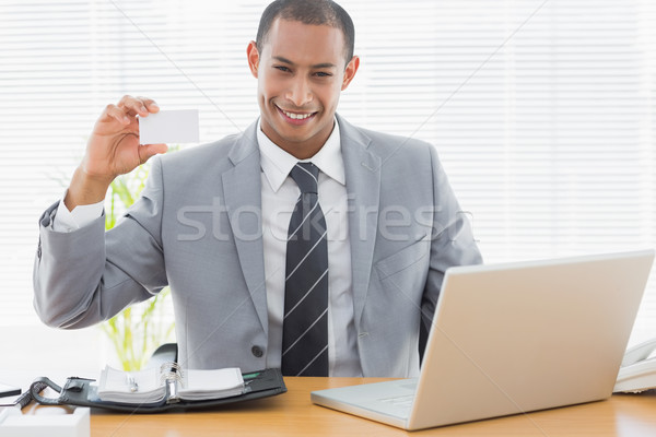 Confident well dressed man with business card at office desk Stock photo © wavebreak_media