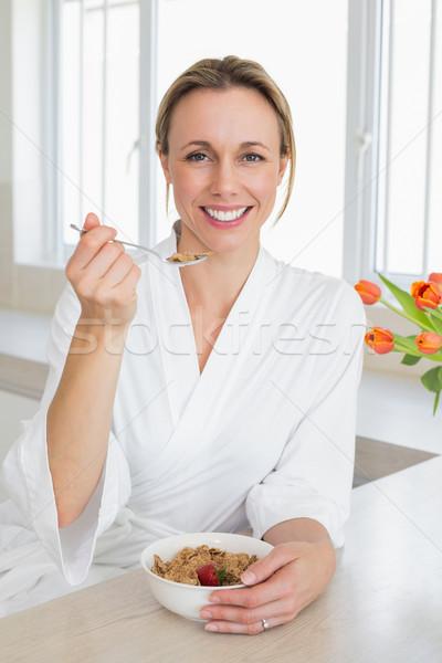 Mosolygó nő fürdőköpeny gabonapehely otthon konyha nő Stock fotó © wavebreak_media
