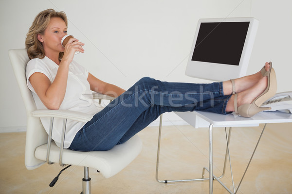 Casual businesswoman having a coffee with her feet up at desk Stock photo © wavebreak_media