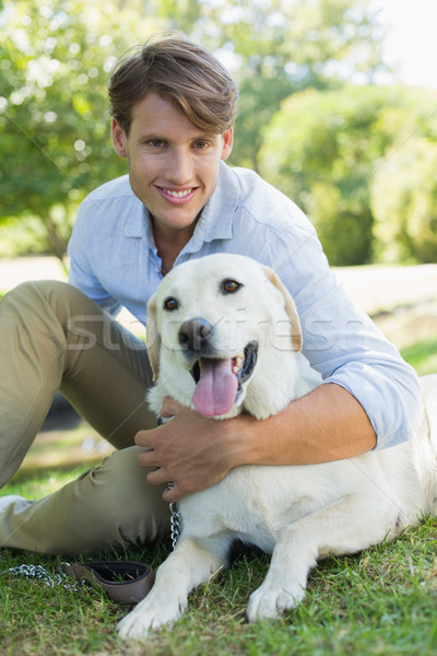 Handsome smiling man with his labrador sitting in the park Stock photo © wavebreak_media