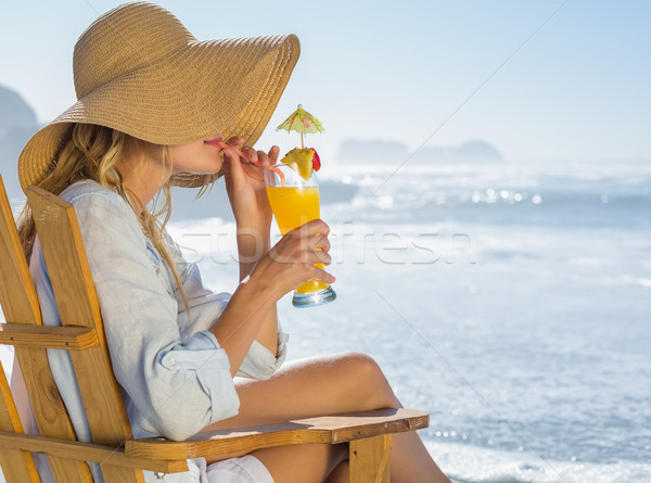 Smiling blonde relaxing in deck chair by the sea sipping cocktai Stock photo © wavebreak_media