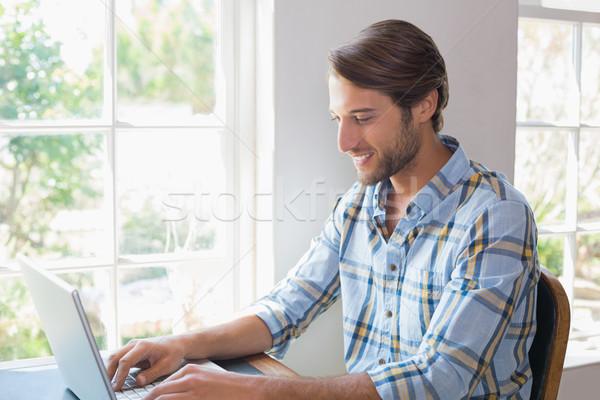 笑みを浮かべて カジュアル 男 ラップトップを使用して ホーム リビングルーム ストックフォト © wavebreak_media