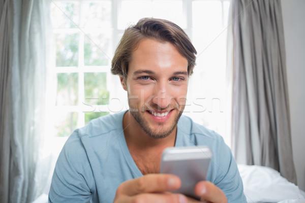 Knappe man vergadering bed home Stockfoto © wavebreak_media