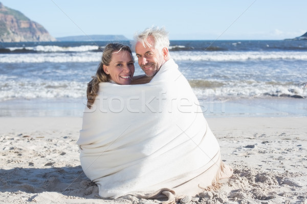 Stock photo: Couple sitting on the beach under blanket smiling at camera