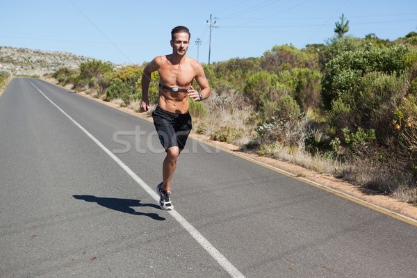Athletic man jogging on open road with monitor around chest Stock photo © wavebreak_media