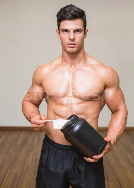Stock photo: Body builder holding a scoop of protein mix in gym