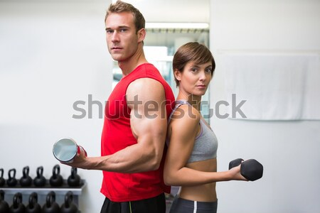 Personal trainer helping client lift dumbbells on exercise ball Stock photo © wavebreak_media