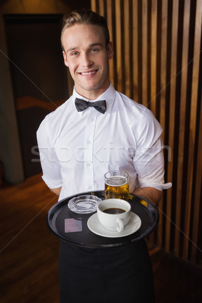 Smiling waiter holding tray with coffee cup and pint of beer Stock photo © wavebreak_media