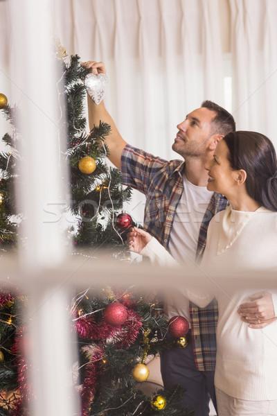 Love couple decorating the christmas tree together Stock photo © wavebreak_media