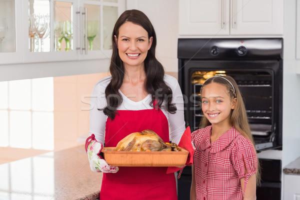 Surprised mother and daughter posing with roast turkey Stock photo © wavebreak_media